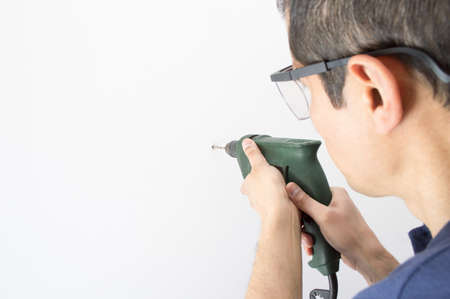 Closeup of a man drilling a hole in wall with goggles protective and space copy photo