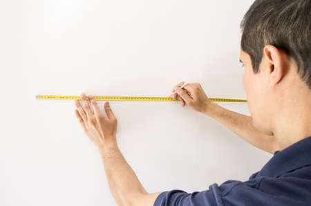 marking up: Closeup of people pointing at a measuring tape on the wall and marking with pencil