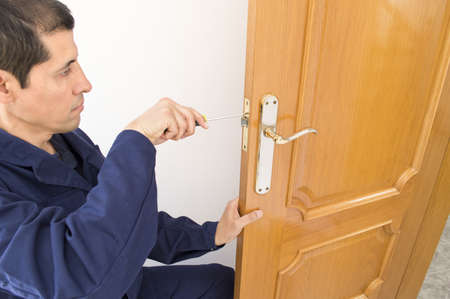 door lock: Carpenter fixing a lock in the door  with a screwdriver