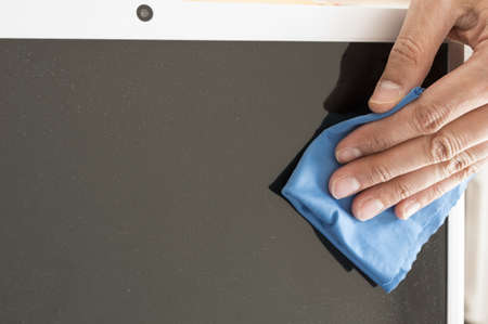 Cleaning a Flat screen with an antistatic cloth blue Imagens