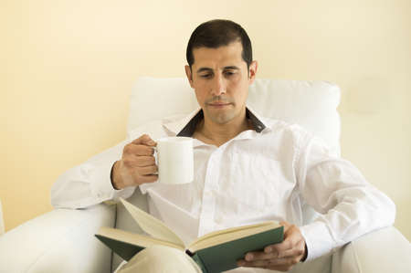 relaxed man reading a book and drinking photo