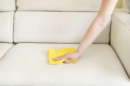 sirvienta: limpieza de un sof� de color beige Foto de archivo
