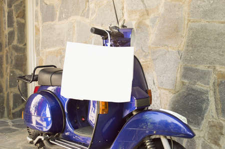 motorcycle parked by a wall of stone with a shopping bag hanging and focus on the white bag photo