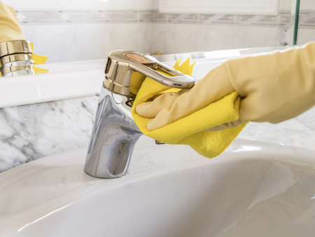 cleanig tap with yellow gloves