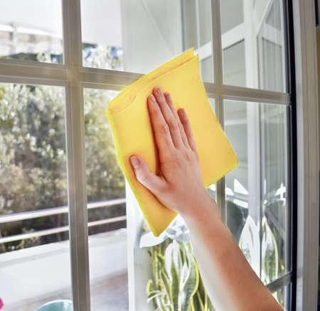 femme nettoyage: Femme de m�nage une fen�tre avec un chiffon jaune Banque d'images