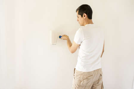man painting white wall with roller photo
