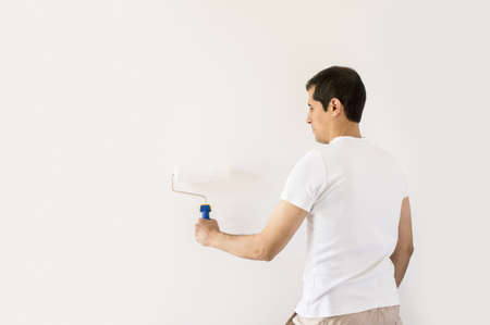 Back side view of a men painting a wall photo