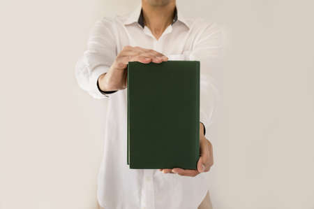 guidebook: man holding up book with green empty book cover in close-up Stock Photo