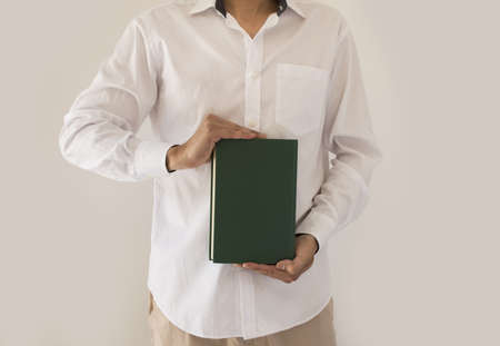 guidebook: man holding up book with green empty book cover