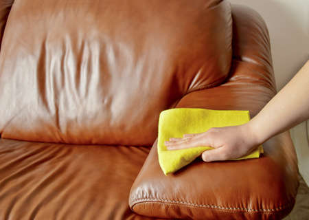 hand wiping couch brown photo