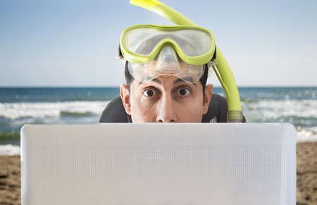 man surprised by the offers for your holidays and trips on the beach Stock Photo