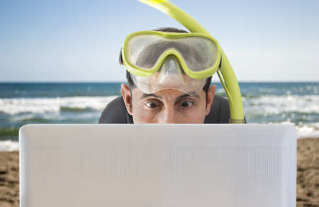 Man surprised by the bid prices on the web for holidays and trips on the beach Stock Photo