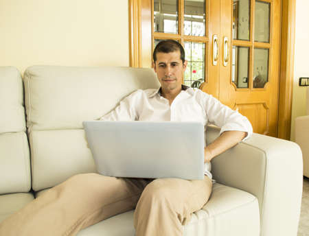 contempory: man working with laptop computer on the sofa