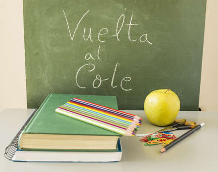 Back to Schoo with pencils, books and an apple in Spanish photo