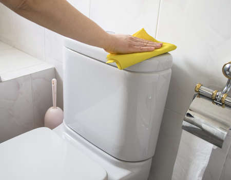 woman cleans a toilet with yellow cloth