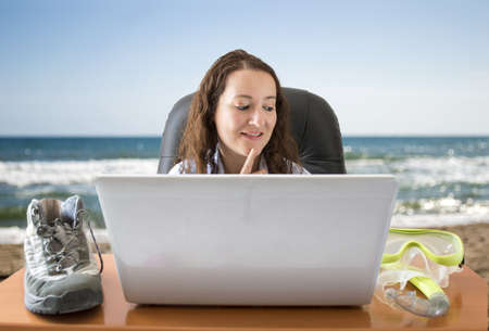 Woman deciding between boots or goggle in front of the laptop with beach background photo