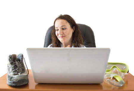 Woman deciding between boots or goggle in front of the laptop photo