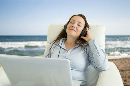 relaxed woman listening music from your laptop  on the beach chill out Stock Photo - 20568425