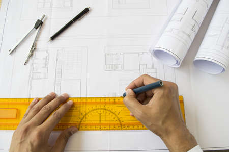 architect drawing: architect designing a plan of a house