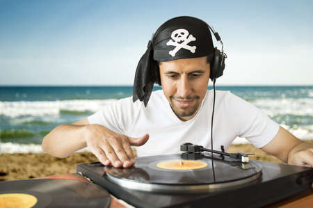 DJ mixing vinyl record on a  turntable with a pirate costume on the  beach Stock Photo - 20997543