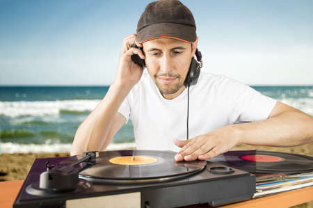 fiesta dj: DJ mezclar discos de vinilo en un tocadiscos con fondo de playa