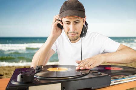 giradisco: DJ vinile miscelazione su un giradischi con sfondo spiaggia