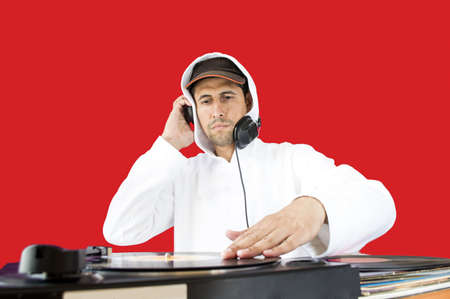 DJ mixing vinyl record on a  turntable with red background Stock Photo - 21171856
