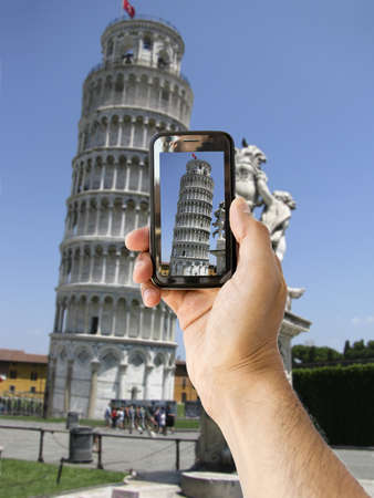 tourist takes a picture with his mobile of  Leaning Tower of Pisa in Italy photo