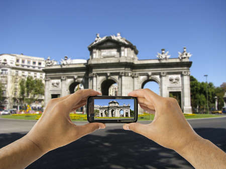 tourist takes a picture with his mobile of Puerta de Alcala in Madrid spain photo