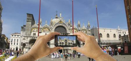 tourist takes a picture with his mobile of the Basilica of San Marco in venice photo