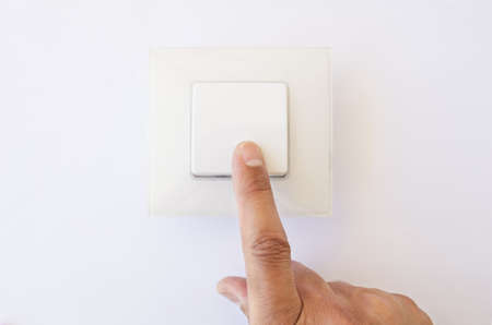 modern light switch being flipped to the OFF position by one finger Stock Photo