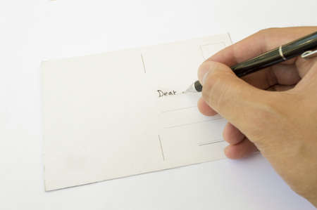 hand writing a postcard to a loved one photo