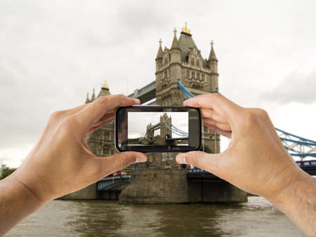 tourist holds up camera mobile at tower bridge in london england photo