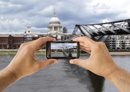 tourist holds up camera mobile photographing at ST Paul Cathedral and  Millennium Bridge  in london england photo