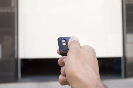 hand pressing a remote control with the door open Stock Photo - 21892439