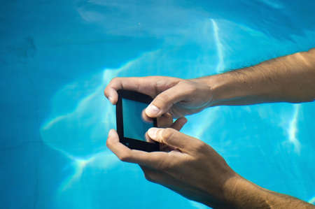 hands by sending a sms on a pool with a waterproof phone photo