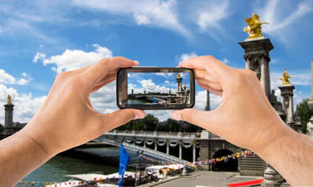 iii: tourist holds up camera mobile at  Pont Alexandre III in  paris france Stock Photo