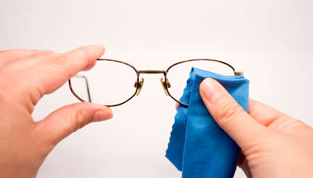 woman cleaning his glasses with blue cloth