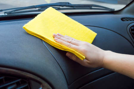man cleaning the car interior with yellow cloth photo