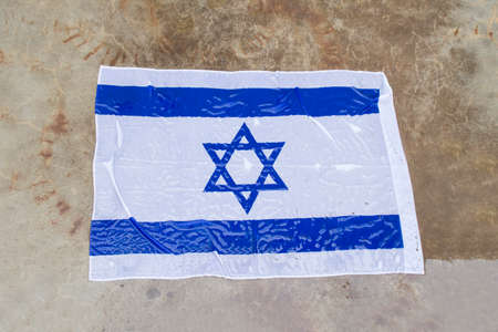 israel flag on the ground in the rain photo