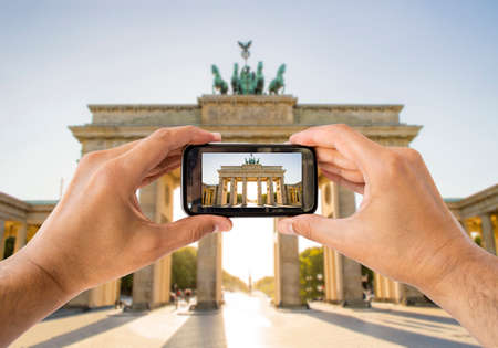 brandenburg gate: tourist taking a picture with your mobile phone brandenburg gate