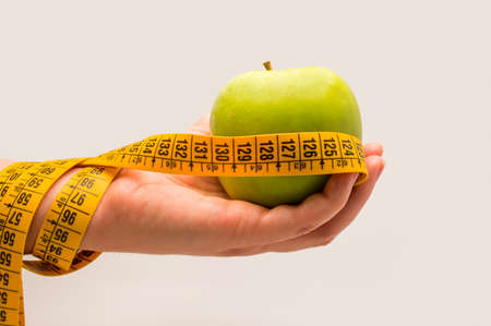 woman hand  showing measurement tape and fresh green apple photo