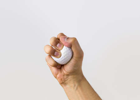 close up human hand squeezing stress ball photo