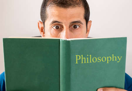 confused man: man reading philosophy makes an expression as he stumbles across something difficult Stock Photo