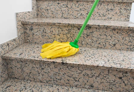 close up of  stairs with yellow mop cleaning