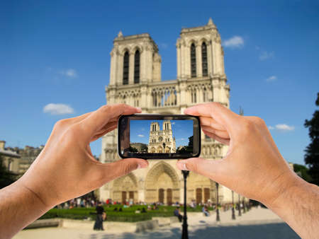 tourist taking a picture with your mobile phone to the cathedral of Notre Dame