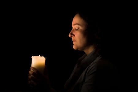 woman holding a candlelight in her hands photo