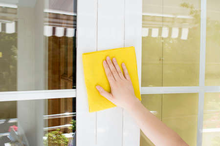 Hand cleaning aluminum window white with yellow cloth