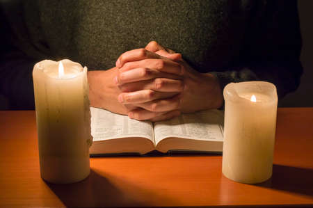 man praying with a bible in the candlelight photo
