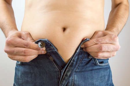 Cropped mid section of an obese man trying to close the buttons of his jeans against